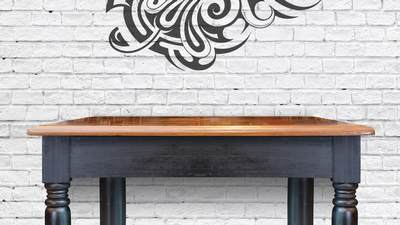A wood desk placed against a white brick wall with a Maori pattern on it.
