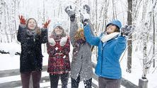 Four smiling, joyful students toss snow up into the air.