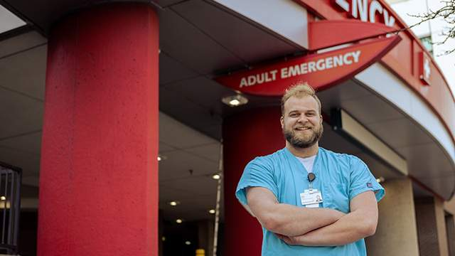 A student in short-sleeved blue scrubs with arms folded in front of hospital's emergency entrance.