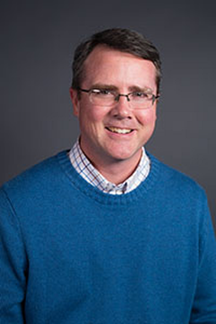 A headshot of a male professor in a blue sweater with glasses