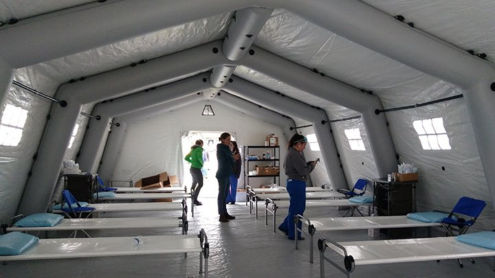 The inside of a tent with beds setup and a few nursing professionals ready to serve patients.