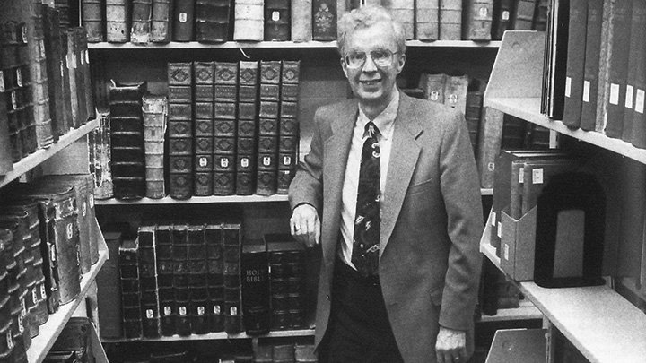 A man in a suit coat and tie stands in a room with bookshelves on three sides.