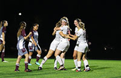 Women's soccer players celebrate a goal in their 4-0 win over Alma on opening night under the lights.
