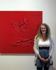 BA Katie Hiskes next to her red dress artwork