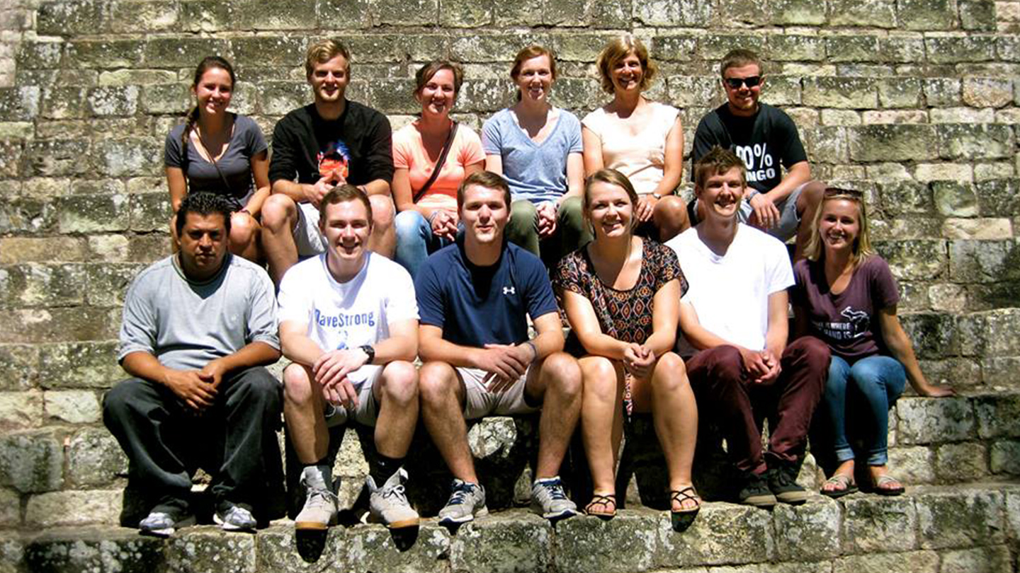 Calvin students on the semester program in Honduras pose for a picture on stone steps.