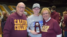 Two grandparents pose with their granddaughter holding a national championship volleyball trophy.