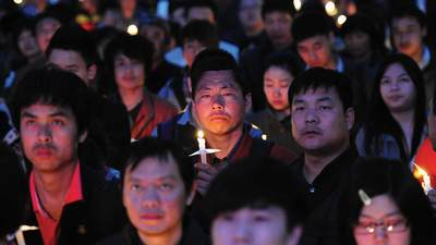 A group of persecuted Christians gather together and hold candles.