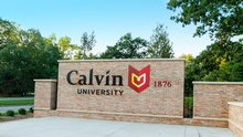 The entrance sign to Calvin University with green trees in the background.