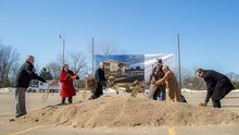 Six people with shovels in hand scoop up dirt in front of a rendering of the new building.