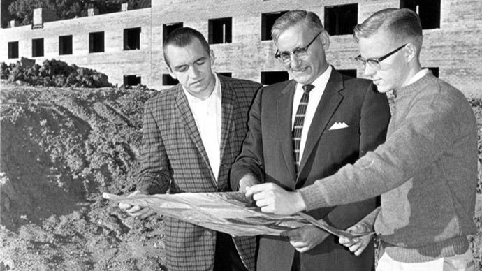 Three men review blueprints at the Knollcrest Campus construction site.