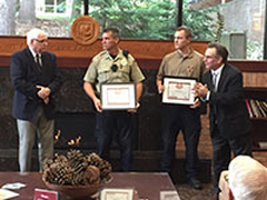 Jim Haan (far right) presents the two officers with their awards and then listens to the remarks from the survivor.