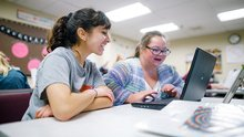 Two students smiling as they work on a computer