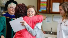 A college student in nursing scrubs hugs a local resident who is receiving a certificate.