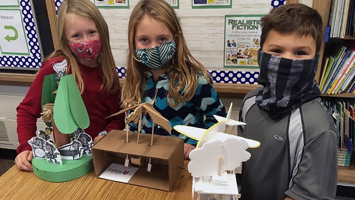 Three second-grade students pose with automatas made by Calvin University engineering students.