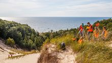 Students standing at the top of a dune along Lake Michigan using research equipment.
