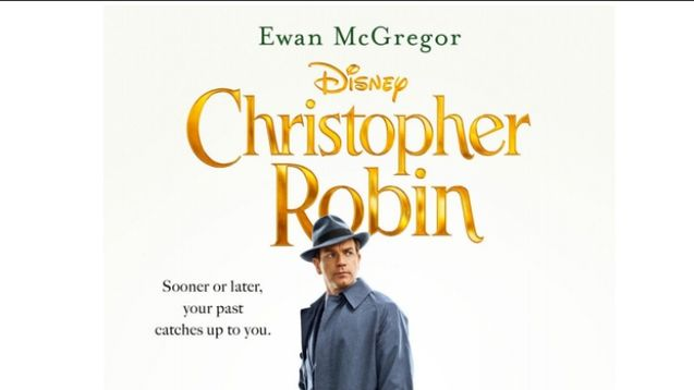Ewan McGregor stands underneath the logo of Christopher robin in a hat, looking off at an indistinct