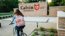 A college student wearing a backpack rides a bike by the Calvin University entrance sign.