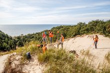 College-age students stand on top of a dune overlooking Lake Michigan doing research.