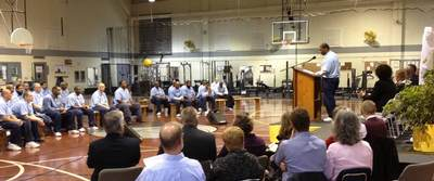 Student inmates gather seated to listen to a speaker from a pulpit.