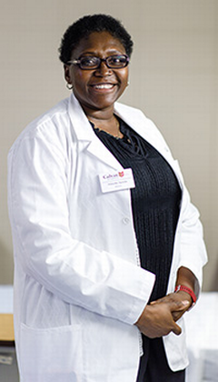 A female professor in a lab coat standing in a classroom smiling
