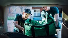 Two college students load a bag of uneaten food into the trunk of a car.