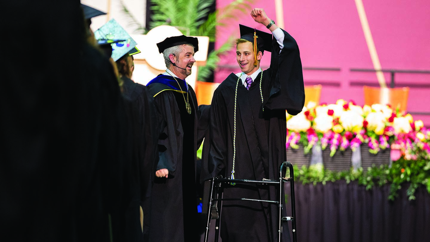 With the help of a walker, Garrett Bazany walks up to receive his diploma beside President Le Roy.