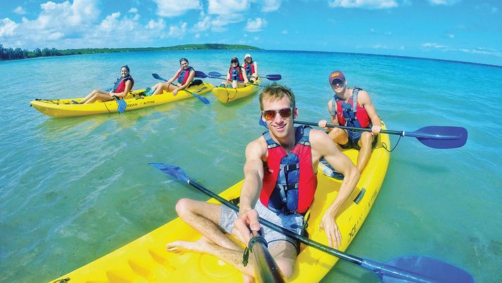 Garrett Bazany and friends kayaking in beautiful clear water.