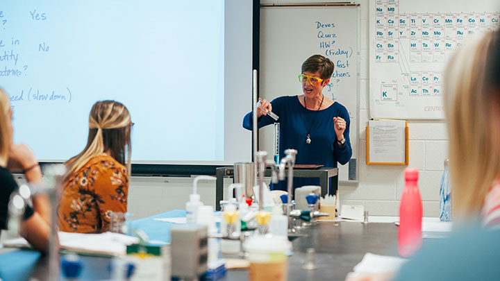 A professor wearing goggles performs an experiment in a lab with students looking on.