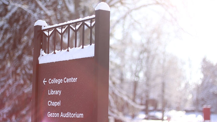 A Calvin College sign with a snowy backdrop.