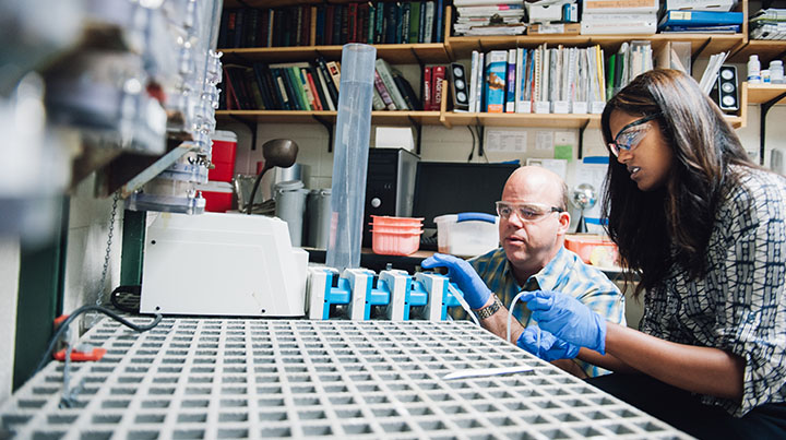 A professor and student sit side-by-side doing water-related research in a lab.