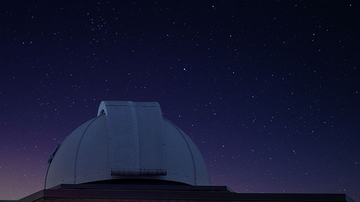 Image of the top of the Calvin Observatory with the night sky in the background