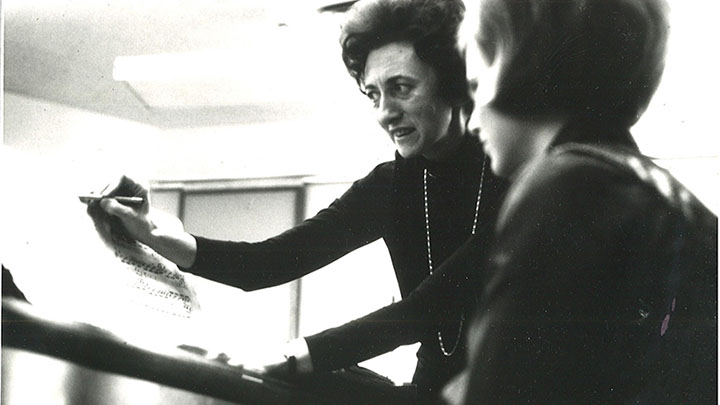 A female music professor standing next to and instructing a student who is seated at the piano.