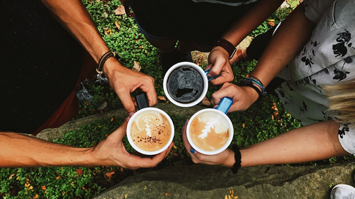 Multiple students' hands holding cups of coffee and hot chocolate drinks
