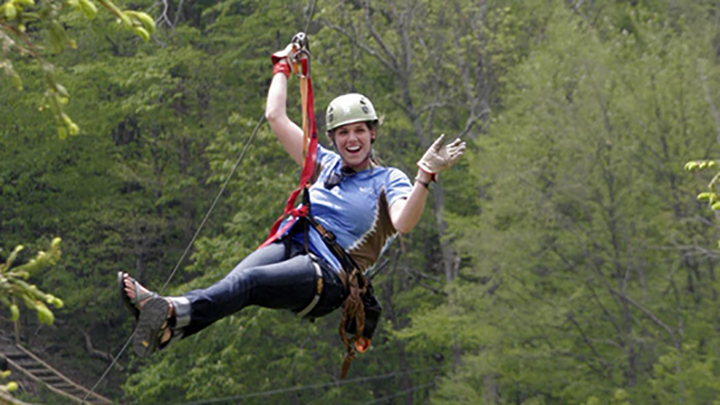 Student riding a zip-line