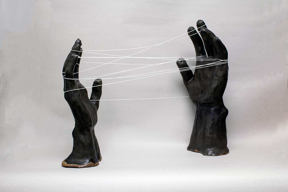 The Space Between Us - Strings intertwining between two hands