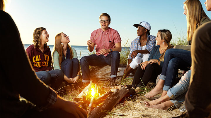 Calvin College students talking around a fire at the beach