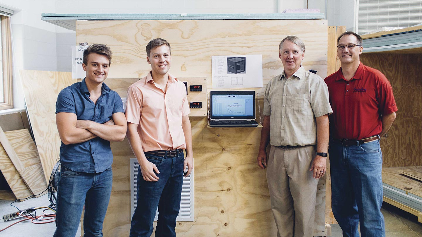 Jonathan Sager, Daniel Wharton, Rich DeJong and Ren Tubergen stand in front of the hotbox, which is being used in the window retrofit project.